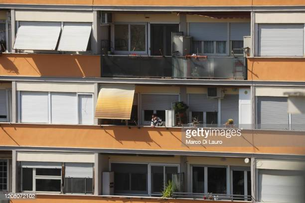 A man talks on his cell phone on the balcony of his apartment during lockdown on March 23 2020 in Rome Italy As Italy extends its nationwide lockdown...