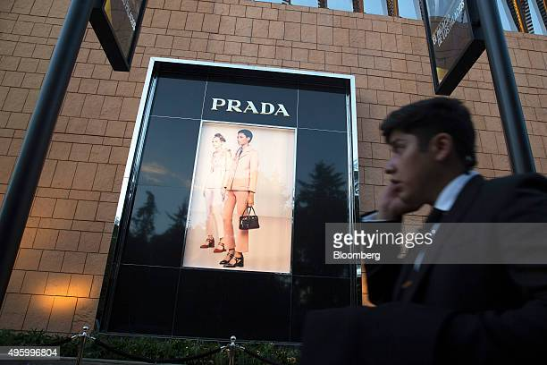 A man talks on his mobile phone as he passes an illuminated Prada sign on the exterior of the building during the reopening of the Palacio de Hierro...
