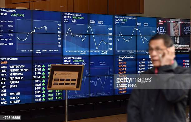 A man talks on his mobile phone as he walks past screens showing trading and foreign currency at the Australian Securities Exchange in Sydney on July...