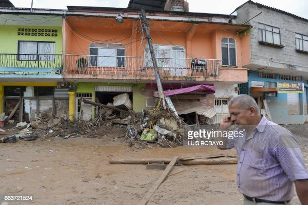 A man talks on his mobile phone on a street damaged by mudslides following heavy rains in Mocoa Putumayo department southern Colombia on April 2 2017...