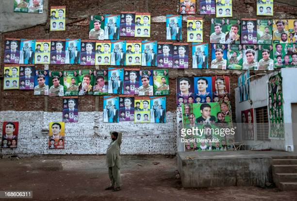 A man talks on his phone as he stands in front of a wall pastered wth PMLN party election campaign posters the day after election day on May 12 2013...
