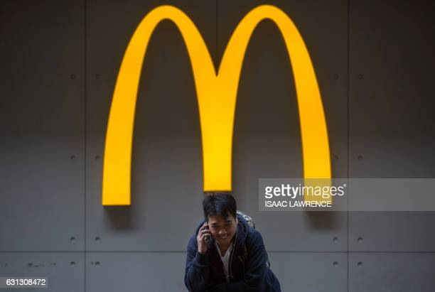 A man talks on his phone outside a McDonalds fast food restaurant in the Admiralty district of Hong Kong on January 9 2017 US fastfood giant...