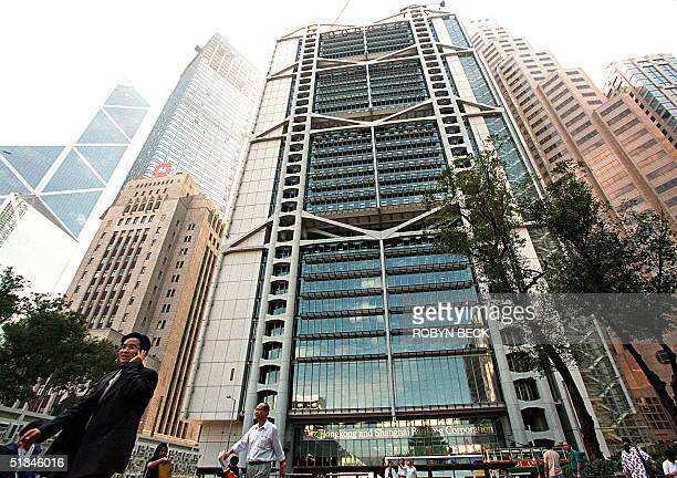 Man talks on his portable phone 16 November as he passes in front of the Hong Kong and Shanghai Bank Building, the Hong Kong headquarters of British...