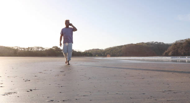 Man talks on phone and walks down empty beach, sunrise