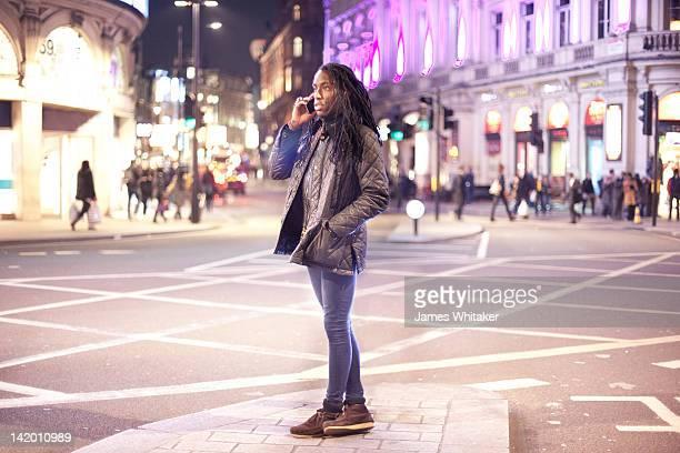 Man talks on phone at city road junction at night