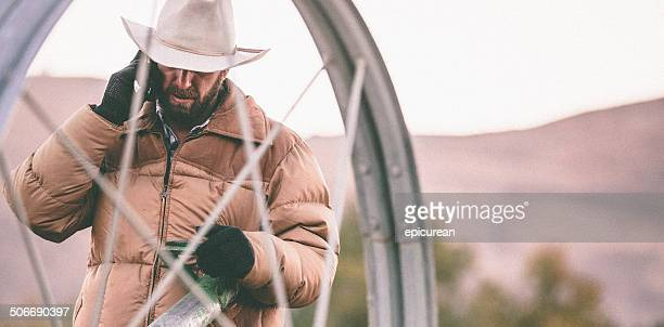 Man talks on phone while working with irrigation equipment