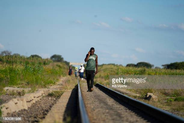 Man talks on the phone as he walks from the Emakhandeni suburb to the Cowdray Park suburb on March 4, 2021 in Bulawayo, Zimbabwe. Despite its...