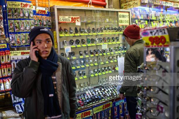 A man talks on the phone as his friend browses discount watches on sale in Ameya Yokocho market on January 4 2018 in Tokyo Japan Ameya Yokocho...