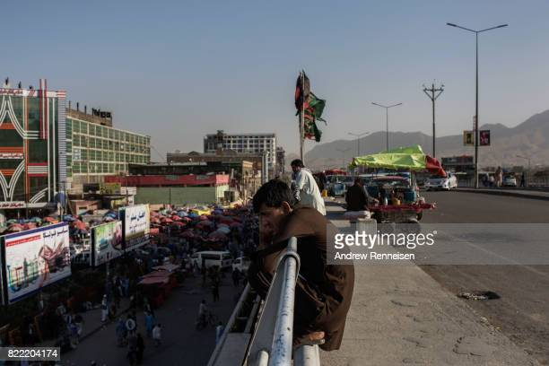 A man talks on the phone on an overpass during rush hour on July 23 2017 in Kabul Afghanistan Despite a heavy security presence throughout the city...
