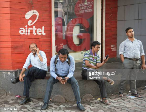 A man talks over a phone in front of the Airtel Store in Kolkata India Airtel improves the performance test which results an improvement with...