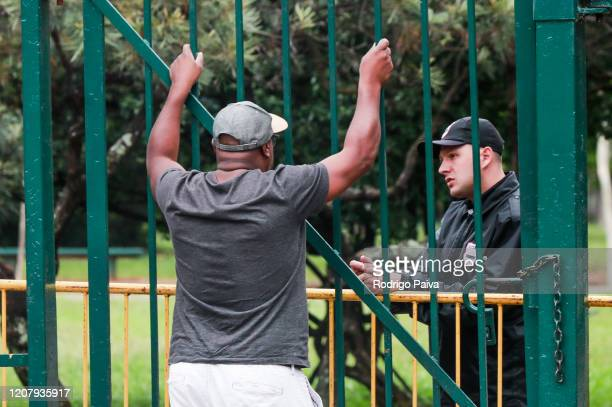 A man talks to a park guard outside the gates of Ibirapuera Park during a lockdown aimed at stopping the spread of the coronavirus pandemic on March...