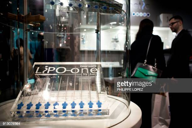 A man talks to a visitor next to liposuction aesthetic surgery needles displayed at a booth of the Aesthetic science plastic surgery and cosmetic...