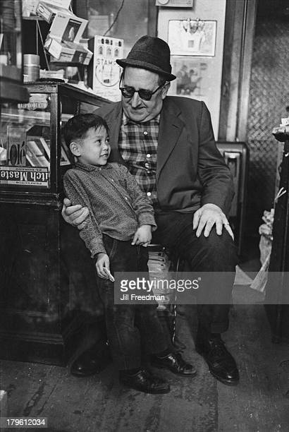 A man talks to a young boy in a candy store in New York City circa 1967