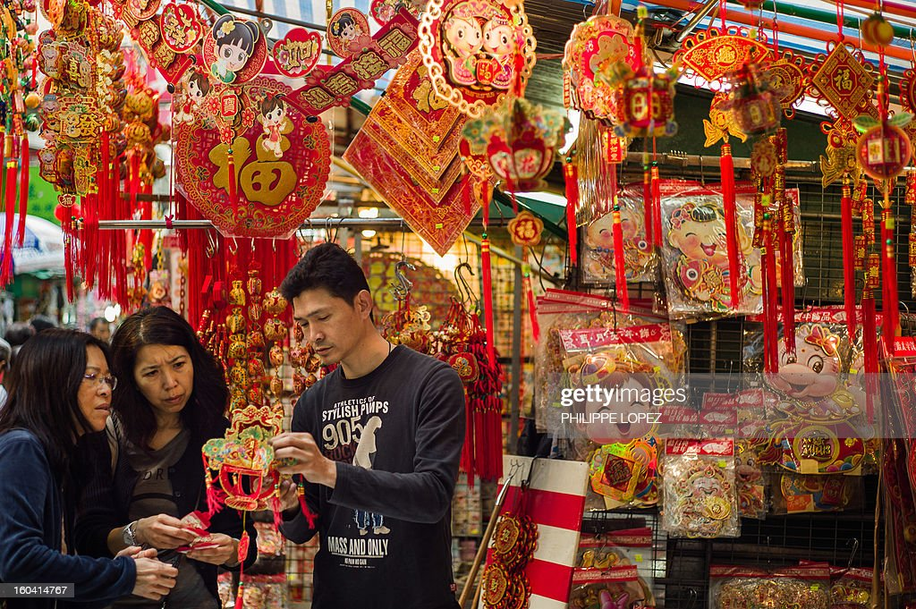 A man talks to customers at the stall of a street market selling Chinese New Year items in Hong Kong on January 31, 2013. The Chinese New Year of the snake falls on February 10, 2013. AFP PHOTO / Philippe Lopez