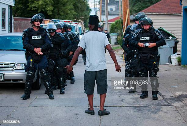 A man talks to police in riot gear as they wait in an alley after a second night of clashes between protestors and police August 15 2016 in Milwaukee...