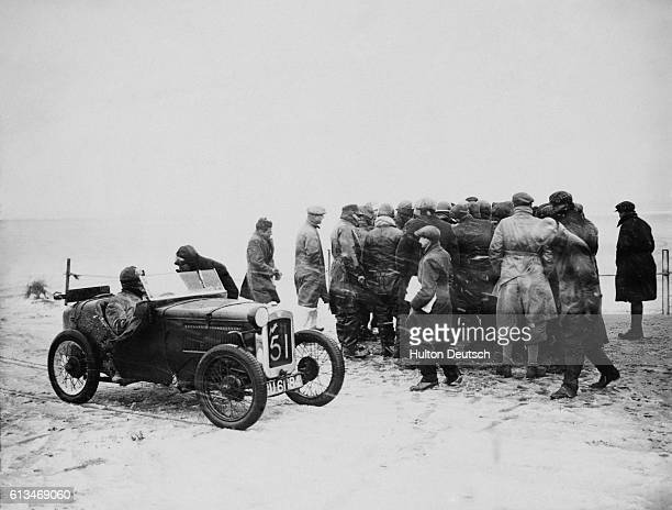 A man talks to racing driver D Z Ferranti sitting his Austin racing car during a blizzard at the Southport Motor Club meeting They are deciding if...