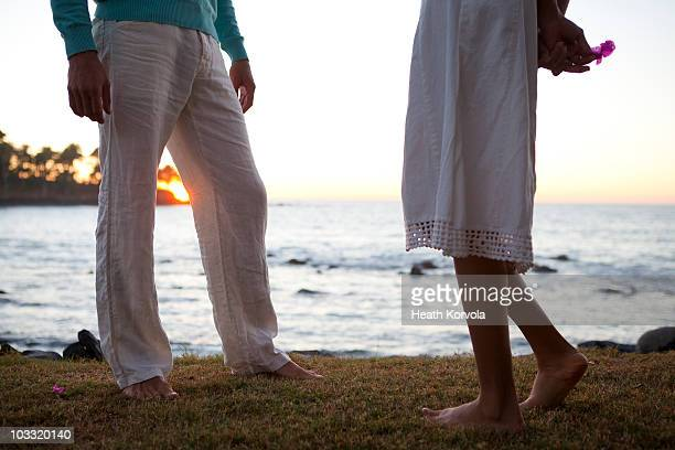 A man talks with a shy woman near the ocean at sunset.