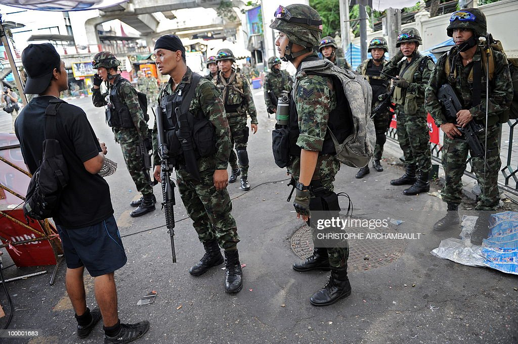 A man talks with soldiers as they make their way into a dismantled anti-government protest zone after gunshots were heard near a Buddhist temple, in downtown Bangkok on May 20, 2010. Gunshots rang out near a Buddhist temple in the heart of an anti-government protest zone in Bangkok, and soldiers were advancing on foot along an elevated train track, an AFP photographer saw. Thai security forces stormed the 'Red Shirts' protest camp on May 19 in a bloody assault that forced the surrender of the movement's leaders who asked their supporters to disperse. AFP PHOTO/Christophe ARCHAMBAULT