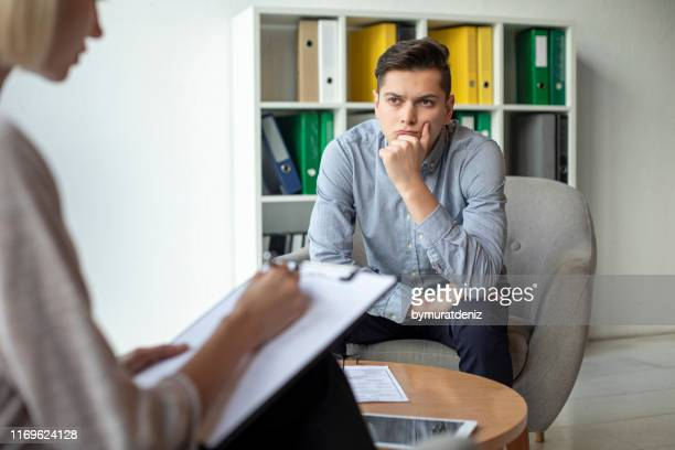 man talks with therapist - social issues stock pictures, royalty-free photos & images