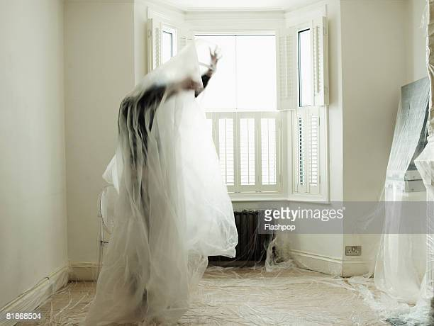man tangled in dust sheets - man wrapped in plastic stock pictures, royalty-free photos & images