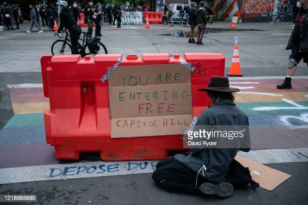 Man tapes a sign to a barricade as demonstrators hold a rally and teach-in outside of the Seattle Police Departments East Precinct, which has been...