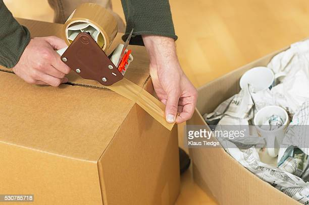 man taping up a cardboard box - tape dispenser stock photos and pictures