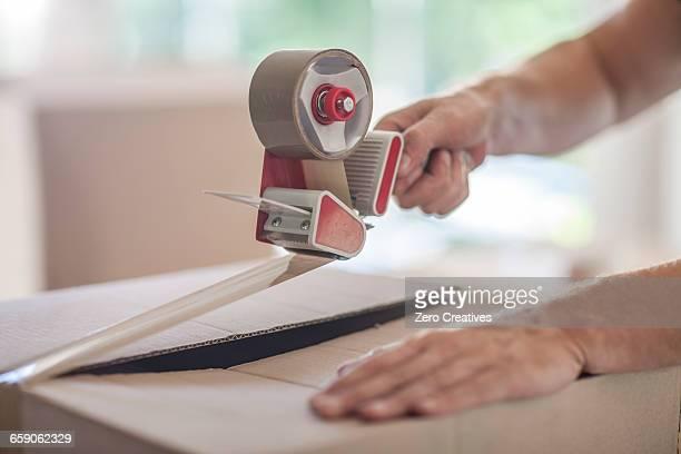 Man taping up box using tape dispenser, close-up
