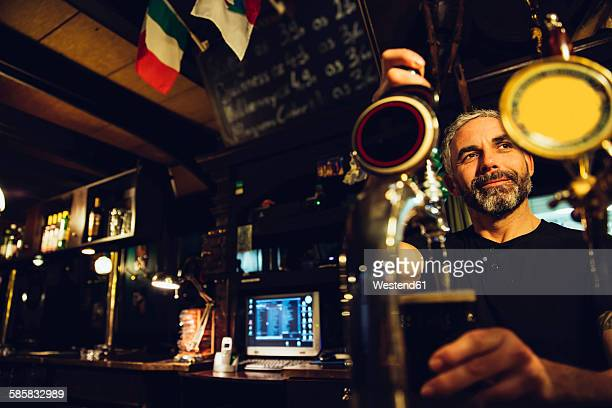 Man tapping beer in an Irish pub