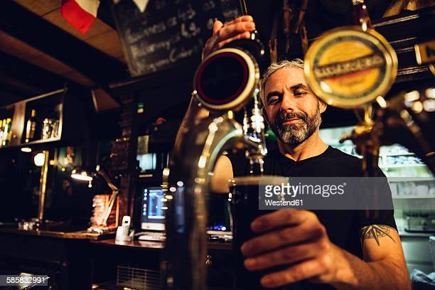 man tapping beer in an irish pub - irish culture stock pictures, royalty-free photos & images