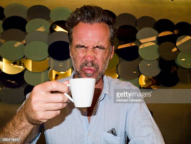 man tasting bitter coffee