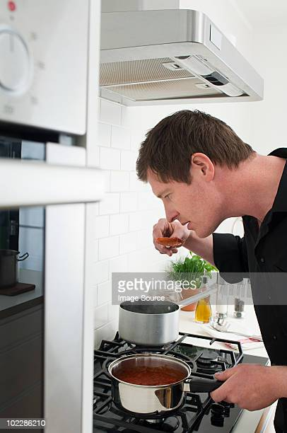 Man tasting food whilst cooking