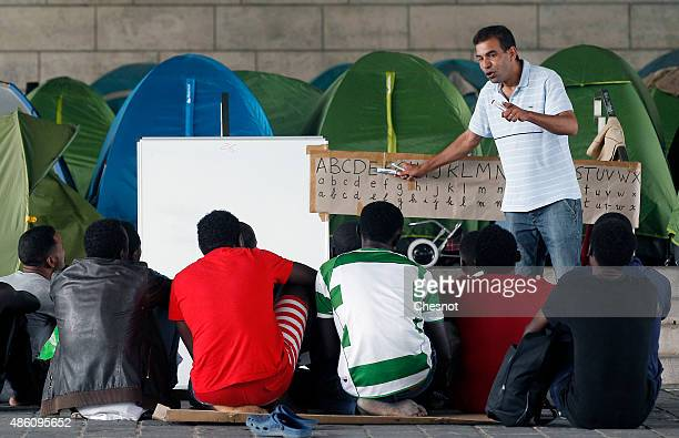 A man teaches the French alphabet to migrants near the Austerlitz train station on August 31 2015 in Paris France Every week refugees arrive who have...