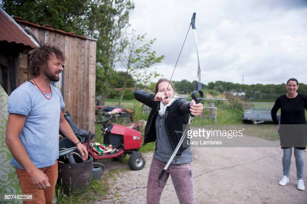 Man teaching a young woman to shoot bow and arrow