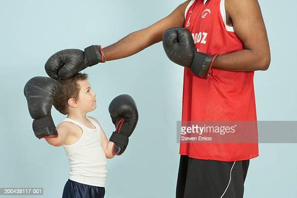 Man teaching boy (5-7) how to box, side view
