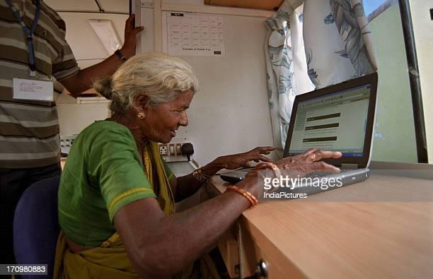 Man teaching computer to an old woman Kuppam Andhra Pradesh India