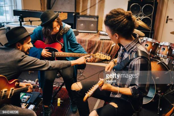 man teaching female friend while playing guitar at recording studio during rehearsals - probe stock-fotos und bilder