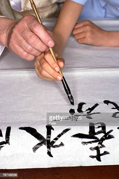 man teaching girl calligraphy - scrittura non occidentale foto e immagini stock