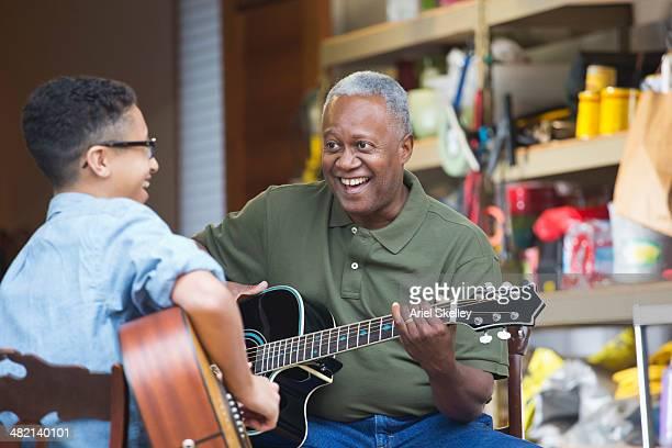 Man teaching grandson to play guitar