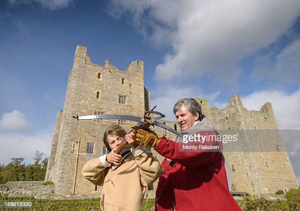 Man teaching history student in period dress how to use crossbow outside Bolton Castle, a 14th century Grade 1 listed building, Scheduled Ancient Monument