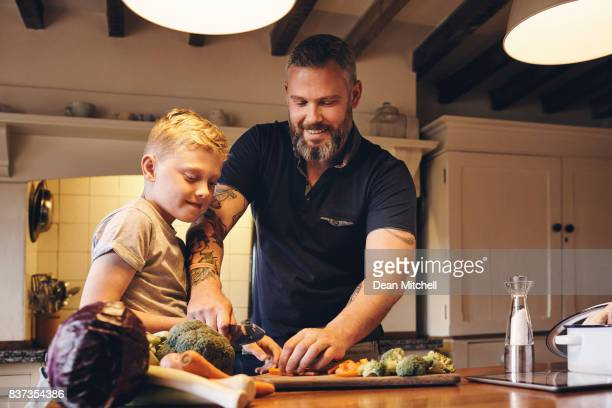 Man teaching how to cut vegetables to his son