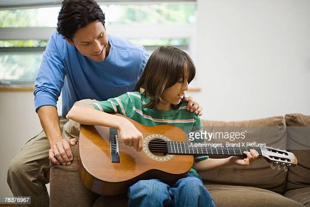 Man teaching teen boy to play guitar