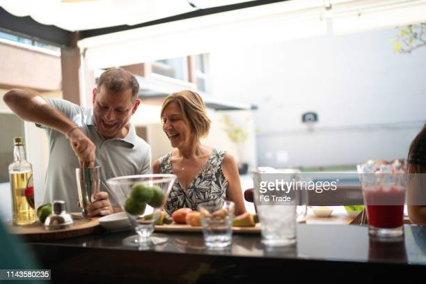 man teaching woman how to make a caipirinha - preparation stock pictures, royalty-free photos & images