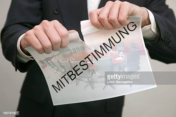 Man tearing a paper with the writing Mitbestimmung Symbol end of the codetermination
