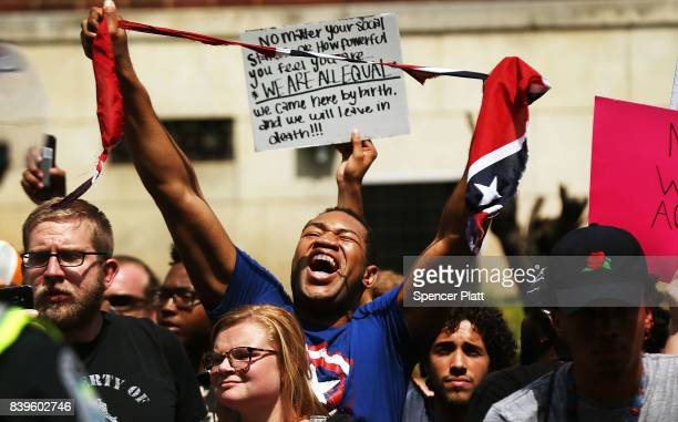 A man tears up a confederate flag as supporters for and against a Fort Sanders Confederate memorial monument face off in on August 26 2017 in...