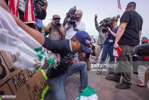 A man tears up a Mexican flag that was taken from a counter protester as supporters of US President Donald Trump rally for the president during his...