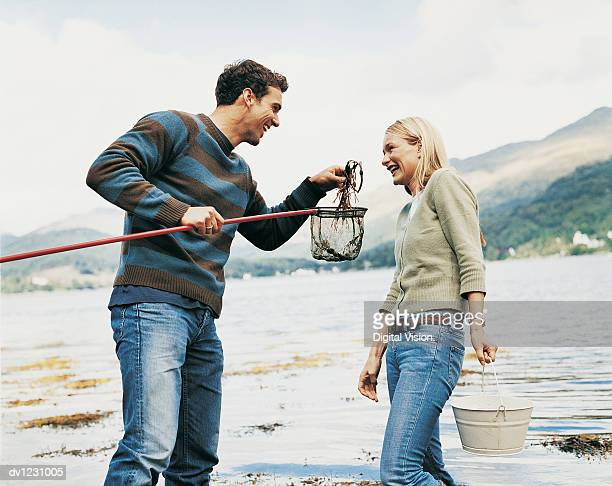 man teasing a woman with seaweed from his fishing net beside a lake - heterosexual couple photos stock photos and pictures