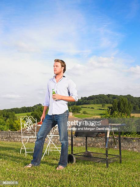 man tending barbecue in front of view