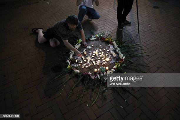 A man tends a makeshift candlelight vigil for those who died and were injured when a car plowed into a crowd of antifascist counterdemonstrators...