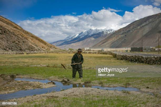A man tends his field in Lukung village which is reliant on solar energy on June 13 2017 in Ladakh India The cold desert of Ladakh has been known as...
