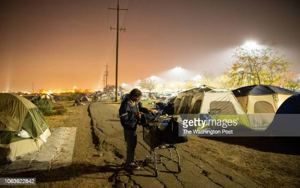 A man tends to his belongings at an evacuee encampment at a Walmart parking lot in Chico California on November 19 2018